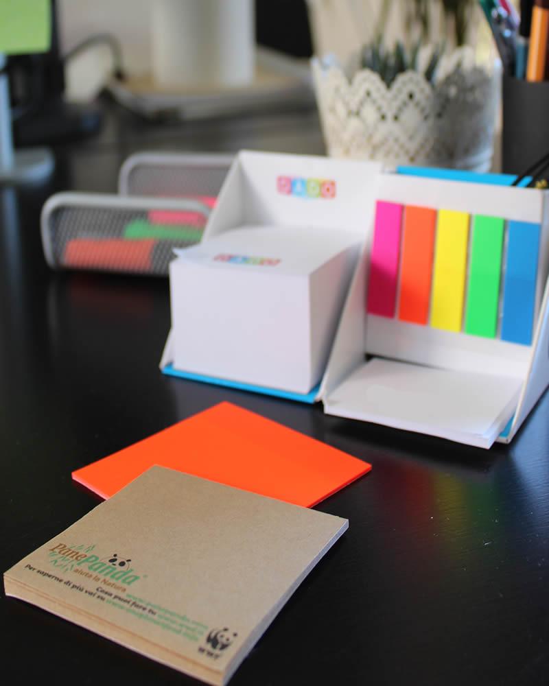 scrivania con post it fluo e con carta ecologica